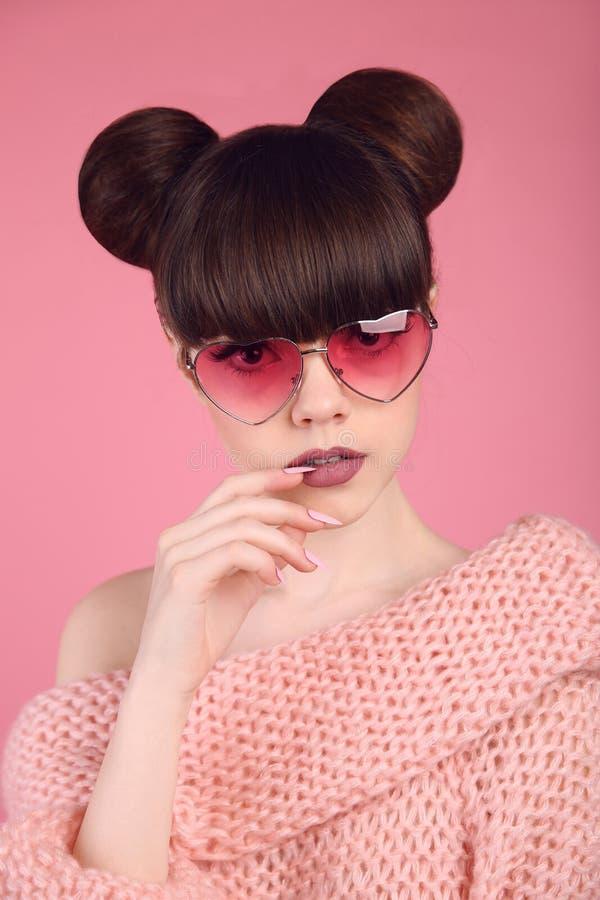 Härlig ung brunett med sungla för hjärta för bullefrisyr bärande royaltyfri bild