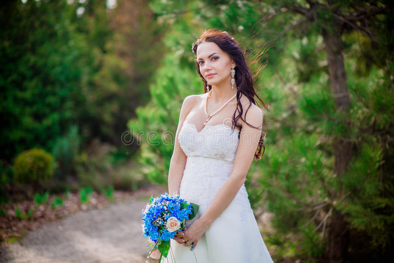 Härlig ung brunettbrud i en vit bröllopsklänning med gardiner, hållande bukett Ukraina royaltyfri bild