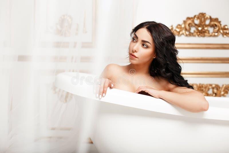 Härlig ung brunettflicka med krullning som vilar i badrummet royaltyfri foto