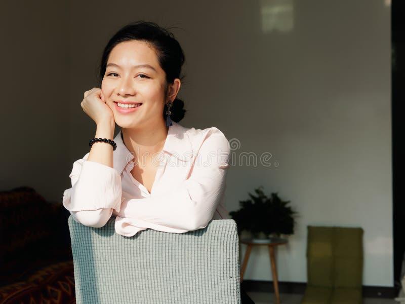 Härlig ung brunettkvinna i den vita skjortan som hemma sitter och ler på kameran i solig dag royaltyfria bilder