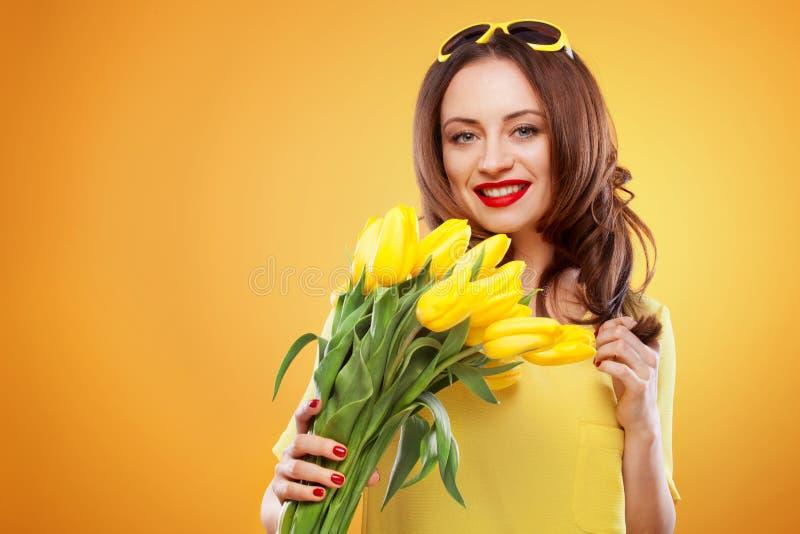 Härlig ung brunettkvinna med gula tulpan på gul bakgrund royaltyfri foto