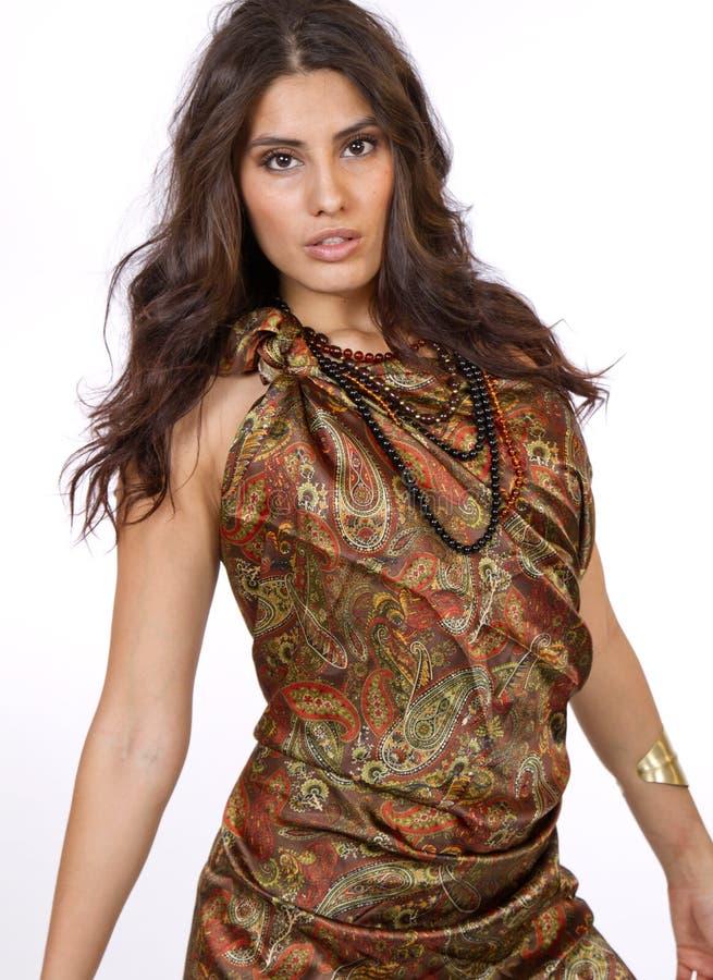 Härlig ung brunettkvinnlig i den paisley klänningen royaltyfri fotografi
