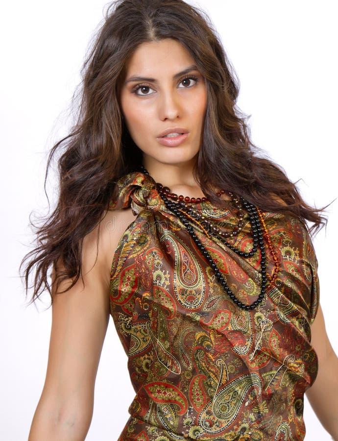 Härlig ung brunettkvinnlig i den paisley klänningen arkivfoto