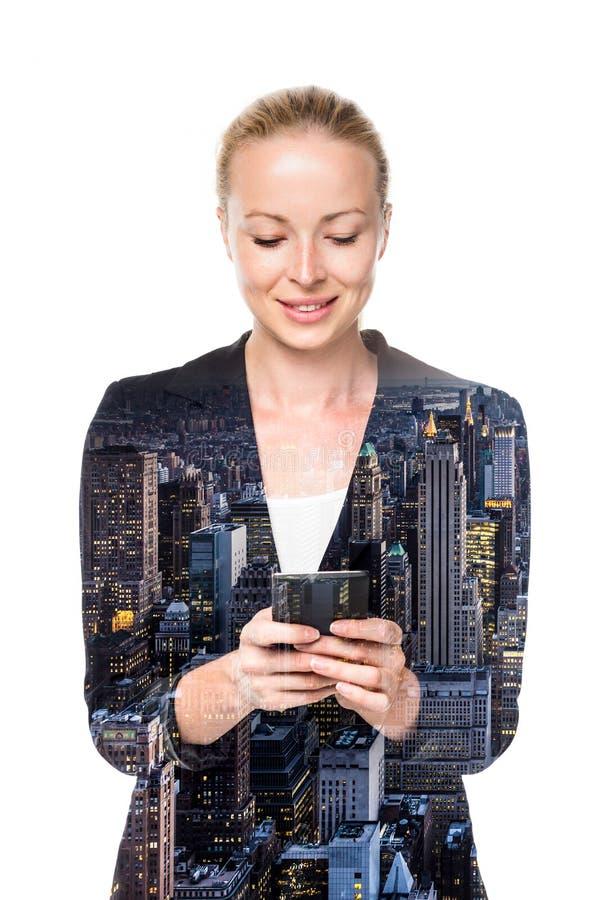 Härlig ung caucasian affärskvinna som använder mobiltelefonen fotografering för bildbyråer