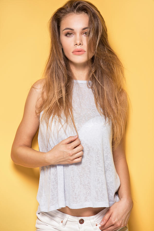 Härlig ung caucasian flicka som poserar på gul bakgrund royaltyfri foto