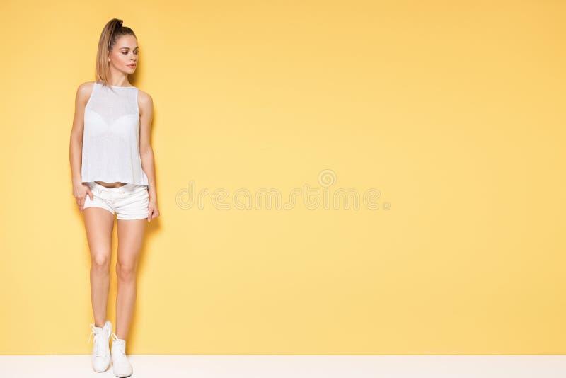 Härlig ung caucasian flicka som poserar på gul bakgrund royaltyfri bild