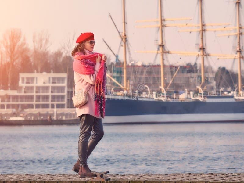 Härlig ung caucasian kvinna i en pläd som går på en träbro, livsstilstående i natur royaltyfria bilder
