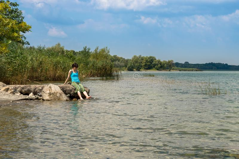 Härlig ung Caucasian kvinna som kyler av i sjön på en sommardag i Sapanca, Turkiet arkivfoto