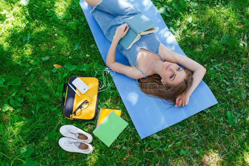 Härlig ung caucasian kvinna som läser en utomhus- bok Ligga på mattt Top beskådar royaltyfria foton