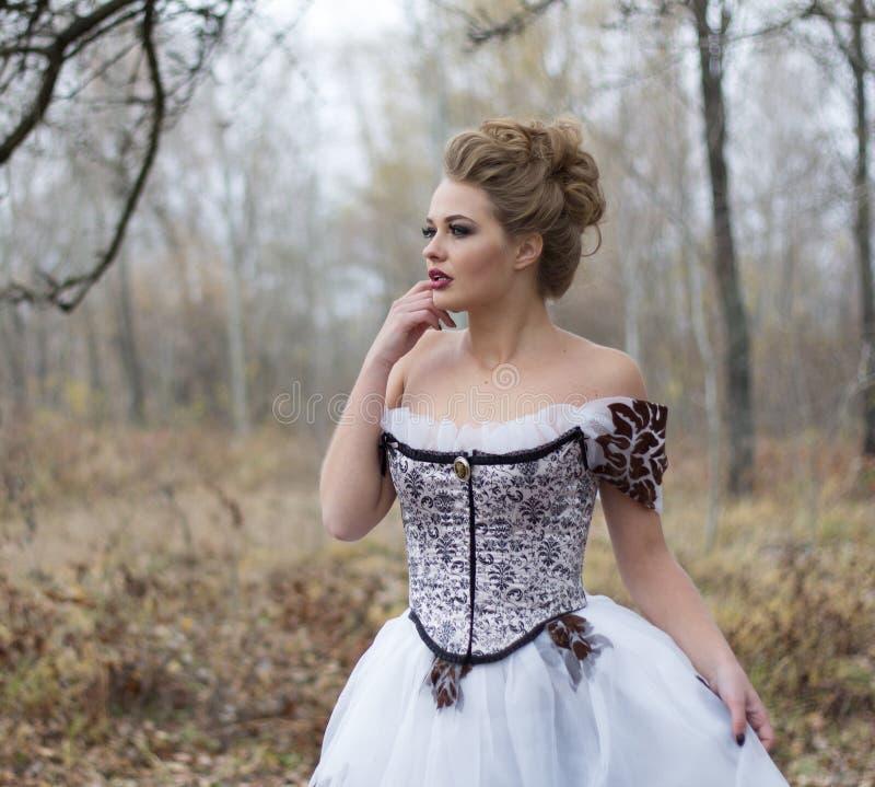 Härlig ung dam i den vita klänningen för ursnygg tappning ståendenolla arkivbild