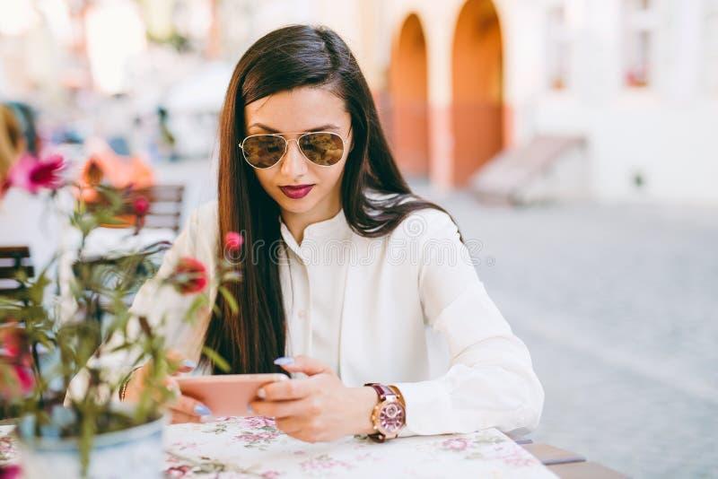 Härlig ung dam som kontrollerar hennes telefon arkivfoto