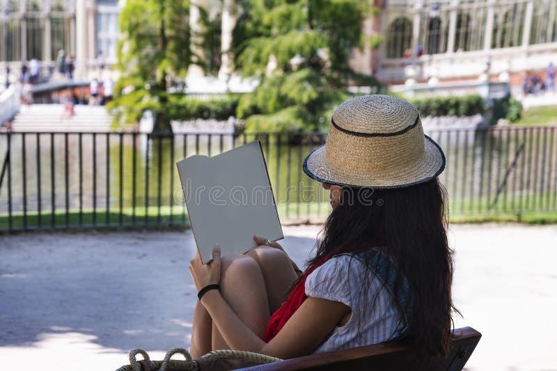 Härlig ung dam som läser en bok i parkera fotografering för bildbyråer