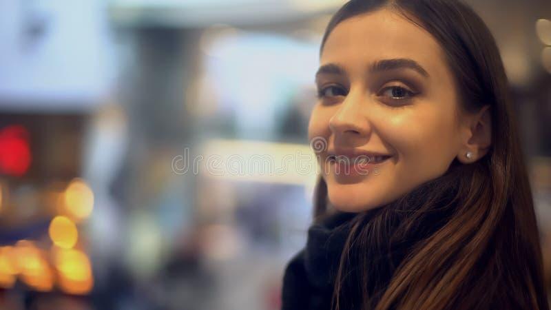 Härlig ung dam som ler till kameran och att stå i järnvägsstationen som reser arkivfoton
