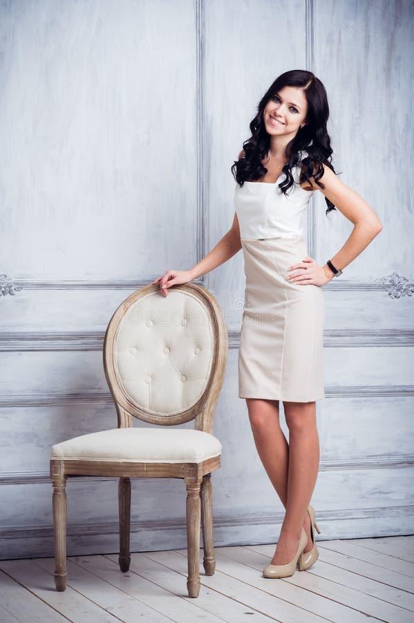 Härlig ung dam som poserar på grå bakgrund med en retro stol royaltyfria foton