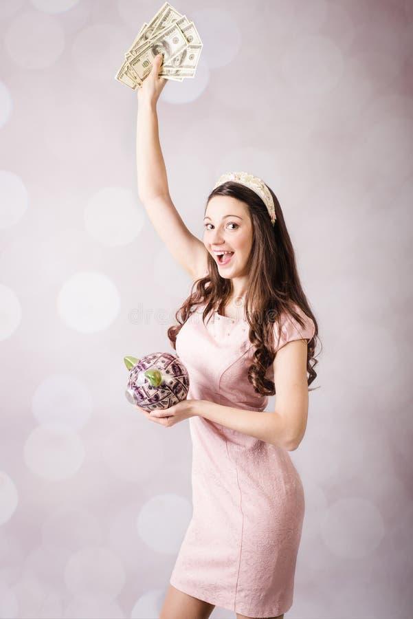 Härlig ung dam som rymmer den USA-sedlar och spargrisen royaltyfria bilder