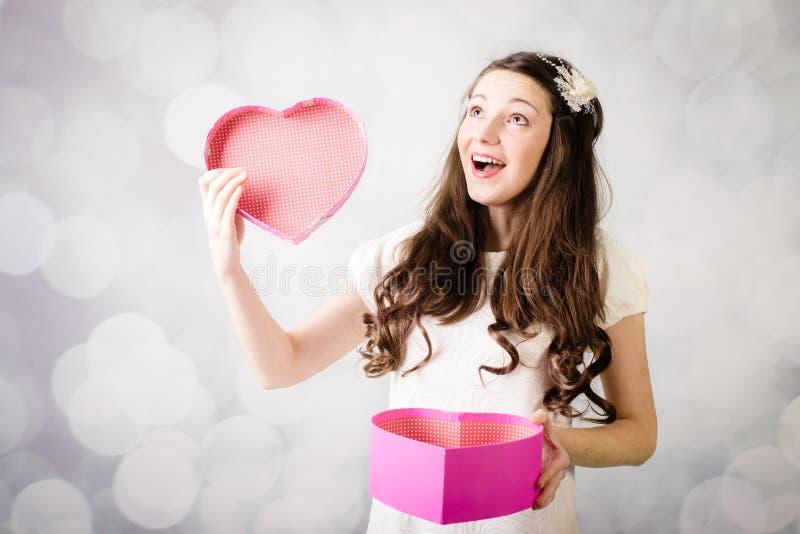 Härlig ung dam som ser hjärtaasken på bokehbakgrund arkivfoto