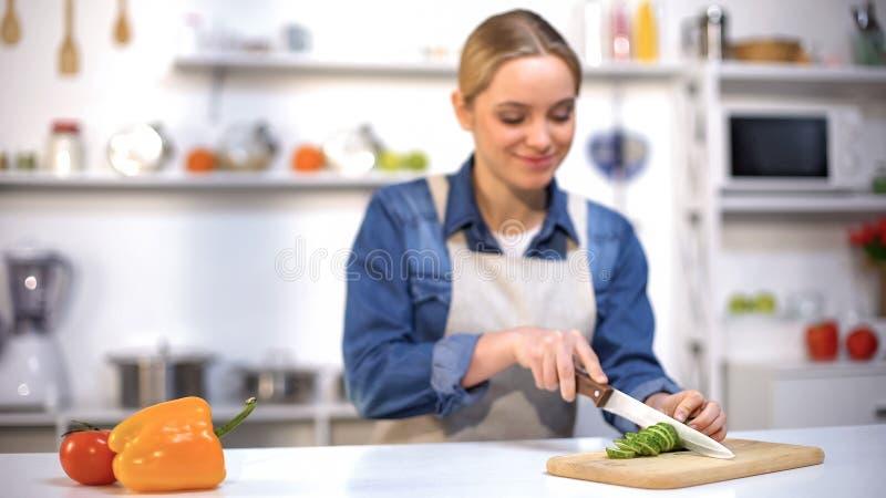 Härlig ung dam som skivar gurkan som förbereder sallad, vegetarisk livsstil royaltyfri foto