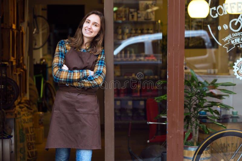Härlig ung försäljare som ser kameran och benägenhet mot dörrramen av ett organiskt lager royaltyfri fotografi