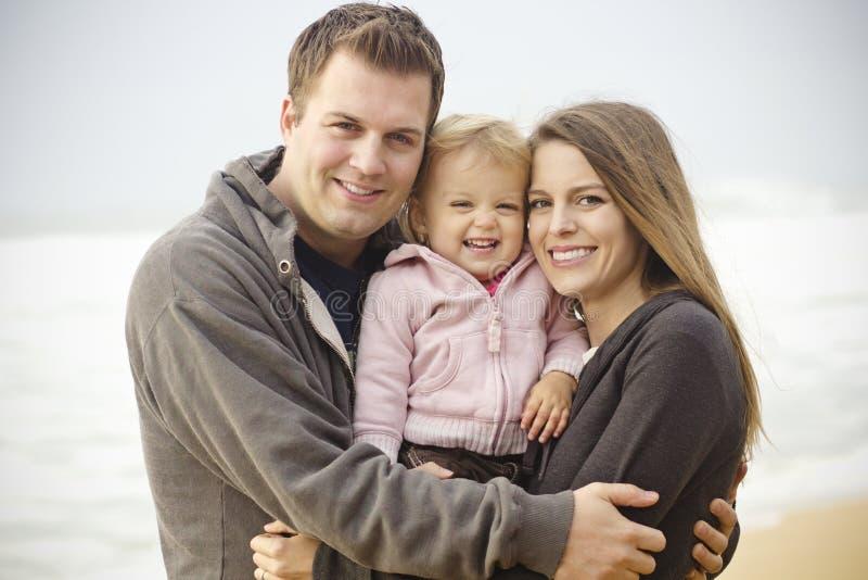 Härlig ung familjstående på stranden arkivbilder