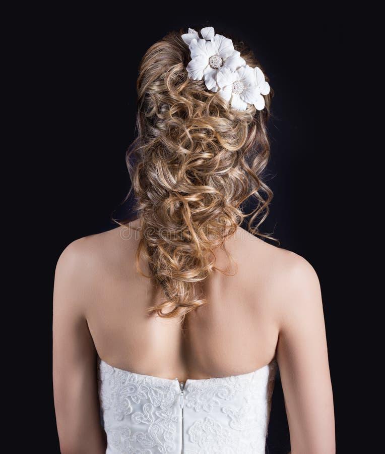 Härlig ung flicka i bilden av bruden, härlig bröllopfrisyr med blommor i hennes hår, frisyr för brud royaltyfri fotografi