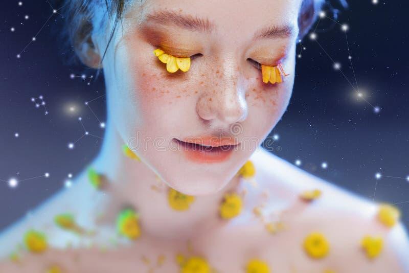 Härlig ung flicka i bilden av flora, närbildstående Sagolik stående på en stjärnklar bakgrund royaltyfri fotografi