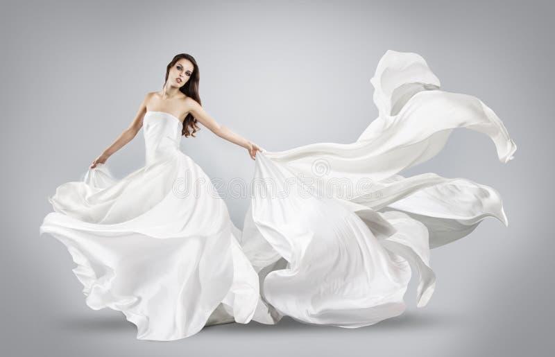 Härlig ung flicka i den vita klänningen för flyg fotografering för bildbyråer