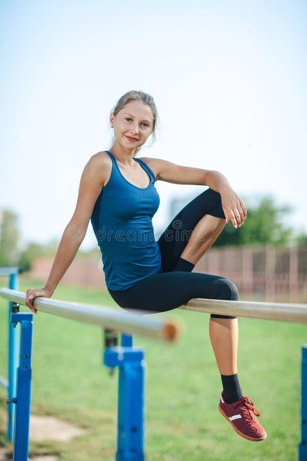 Härlig ung flicka i en blå skjorta och damasker som sitter på de ojämna stängerna, på de utomhus- sportarna som malas i sommar so arkivfoto