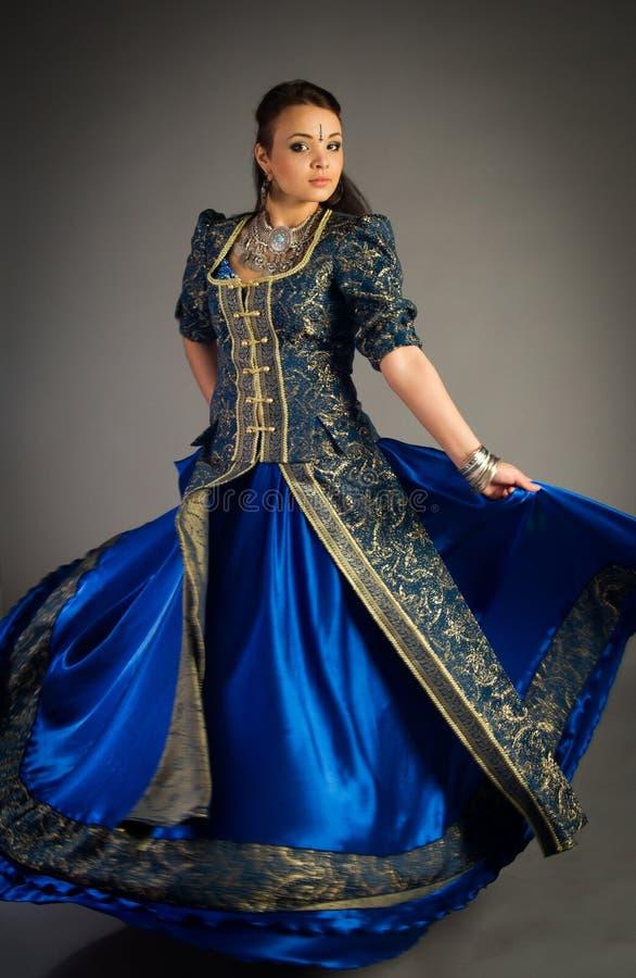 Härlig ung flicka i en historisk klänning arkivfoto