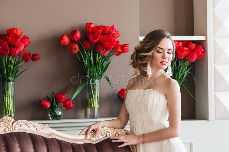 Härlig ung flicka i en vit klänning som poserar i en inre studio som dekoreras med stora buketter av röda tulpan royaltyfria bilder