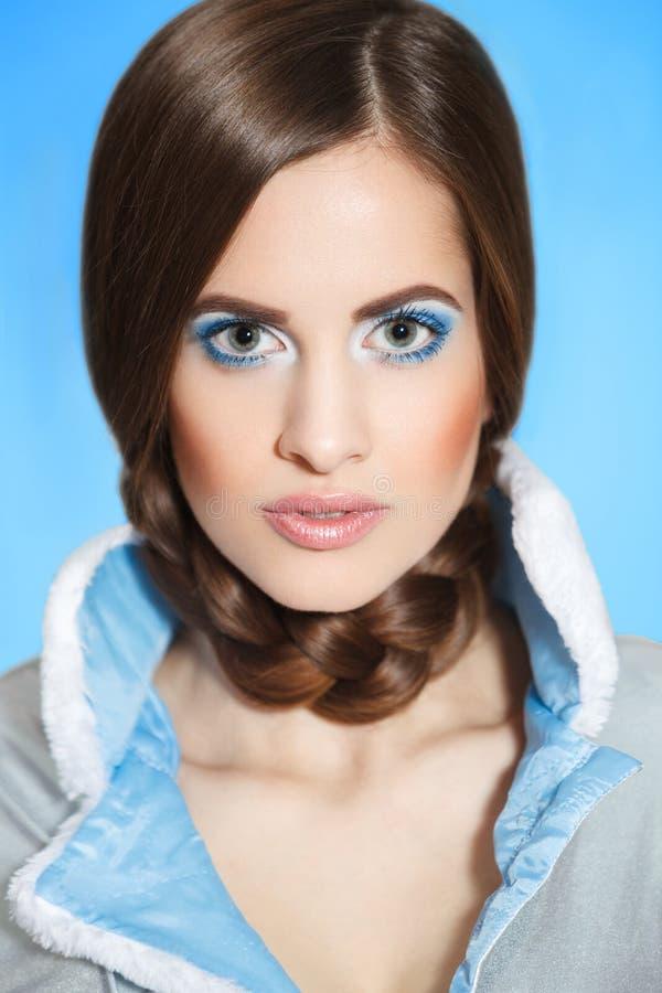 Härlig ung flicka i ett blått pälslag med en vit krage med ljust smink och blåa ögon Stående Mode skönhet, vinter, royaltyfri fotografi