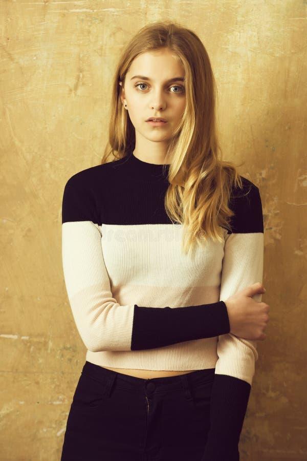 härlig ung flicka i flåsanden och ärmlös tröja på väggbakgrund royaltyfri fotografi
