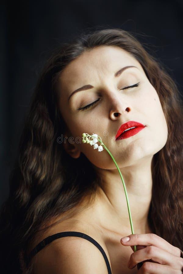 Härlig ung flicka i läderomslaget som poserar i studio på svart isolerad bakgrund I händerna av kvinnor blomma St?ende royaltyfri fotografi