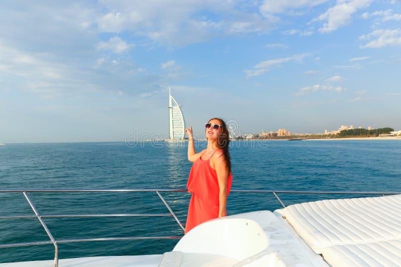 Härlig ung flicka i röd klänning på yachten royaltyfri bild