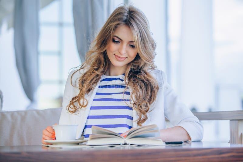 Härlig ung flicka i utomhus- kafé läsande a arkivbild