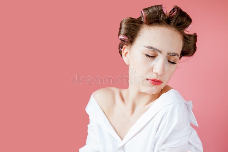 Härlig ung flicka med en maskering och hårrullar som trycker på hennes framsida arkivbild