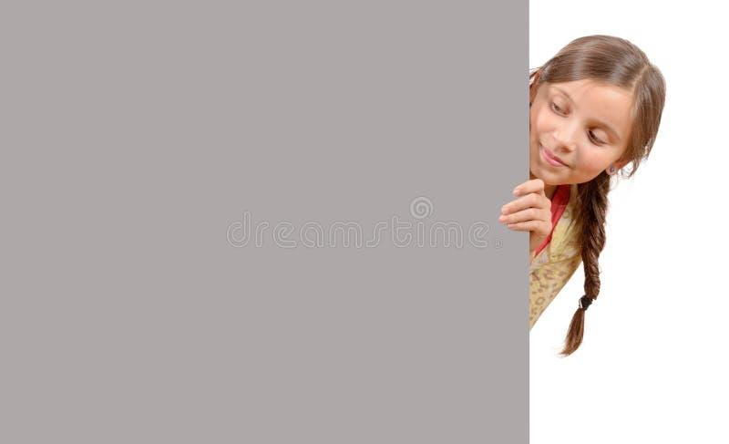 Härlig ung flicka med en tom affisch som isoleras på vitbaksida royaltyfria bilder