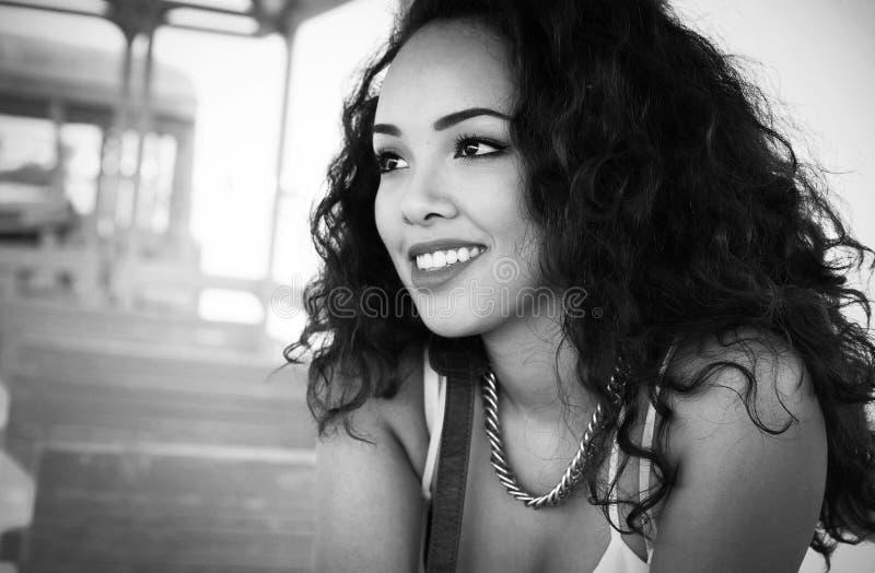 Härlig ung flicka med lockigt brunt hår, brun hud och den halva kroppståenden för nätt leende, blick för modemodell, skönhetfoto royaltyfria bilder