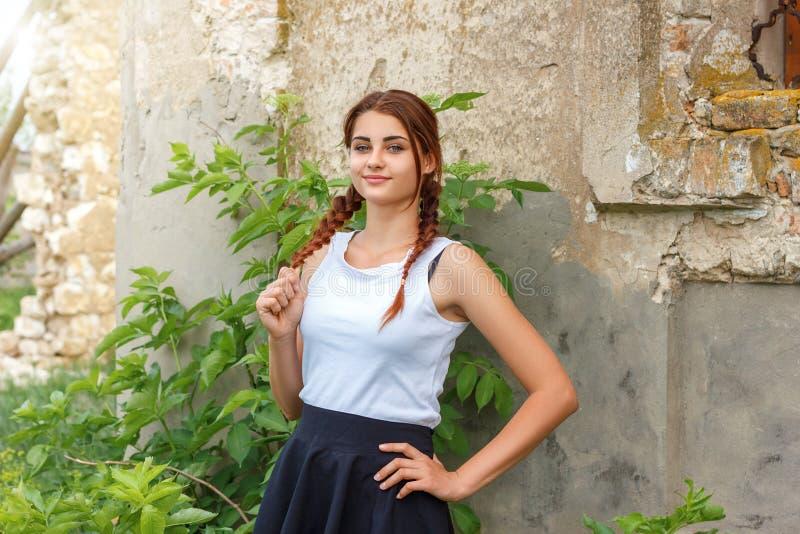 Härlig ung flicka med råttsvansar som står nära en tegelstenvägg royaltyfri fotografi