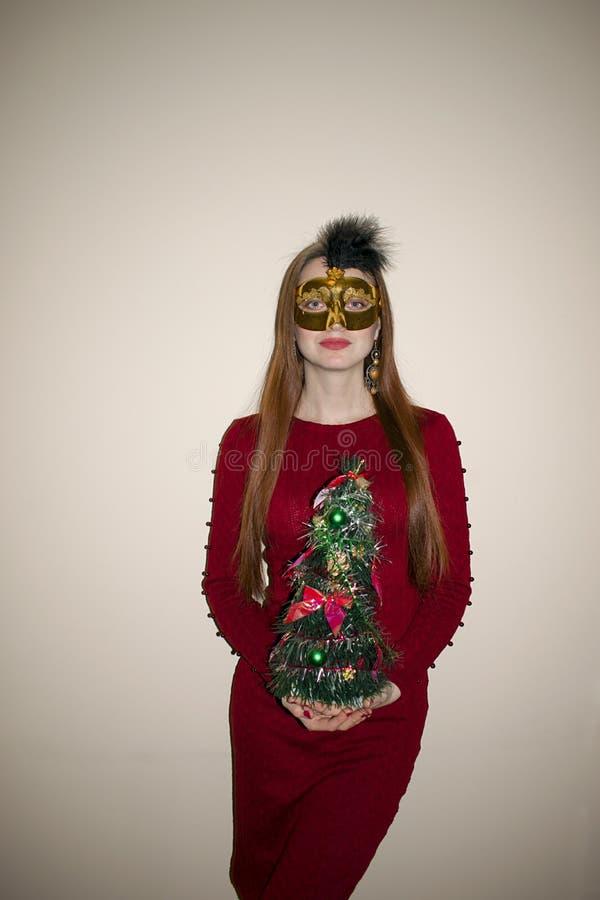 Härlig ung flicka med rött hår i en gul maskering arkivbild