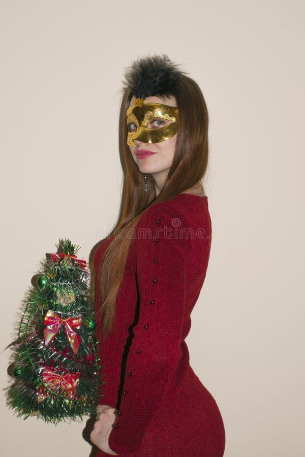 Härlig ung flicka med rött hår i en gul maskering royaltyfri bild