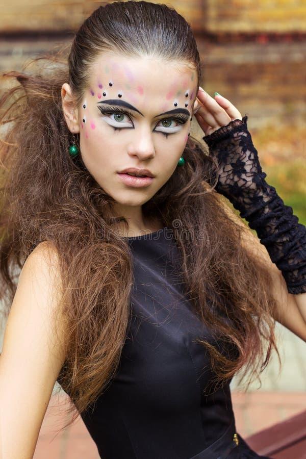 Härlig ung flicka på bakgrunden av sidorna i höstdag på gatan med fantasimakeup i en svart klänning royaltyfria bilder