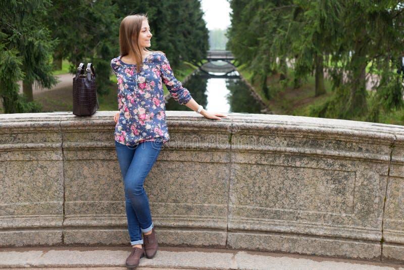Härlig ung flicka på den gamla stenbron royaltyfria foton