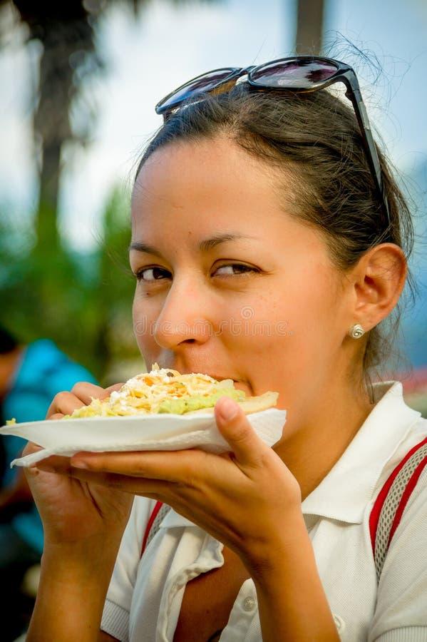Härlig ung flicka som äter en mjuk taco för tostada royaltyfri fotografi