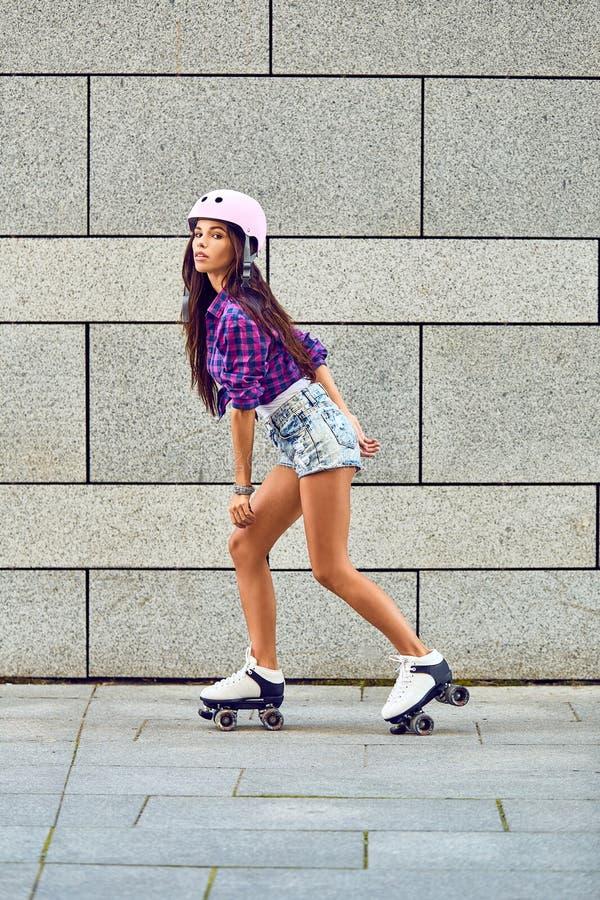 Härlig ung flicka som åker skridskor på rullskridskor fotografering för bildbyråer
