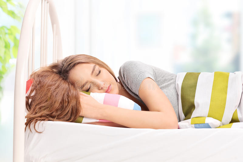 Härlig ung flicka som bekvämt sover på en säng royaltyfri foto