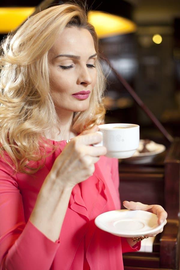 Härlig ung flicka som dricker kaffe royaltyfri bild