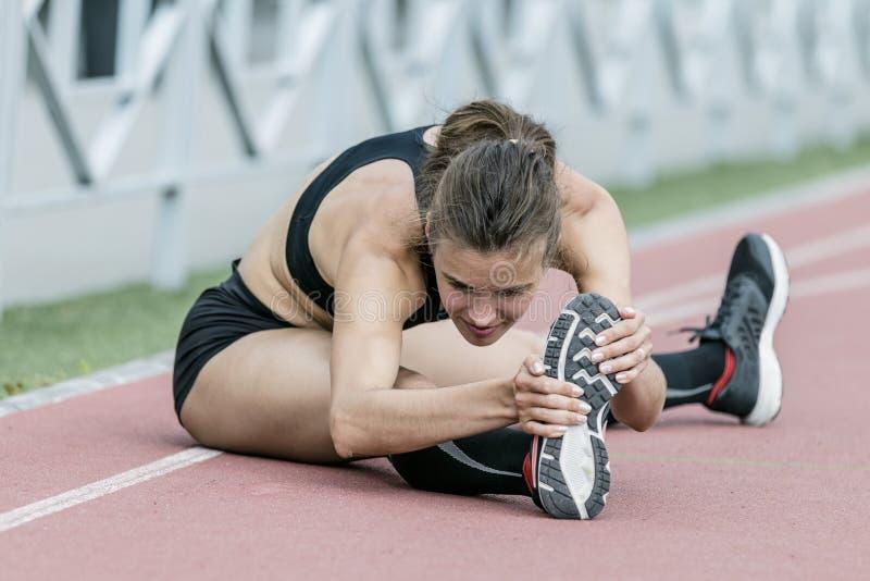Härlig ung flicka som gör övning i stadion royaltyfria foton