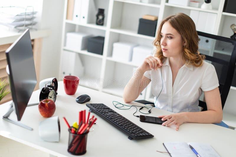 Härlig ung flicka som i regeringsställning arbetar med datoren Flickan har en skalm och en telefon framme av henne arkivbild