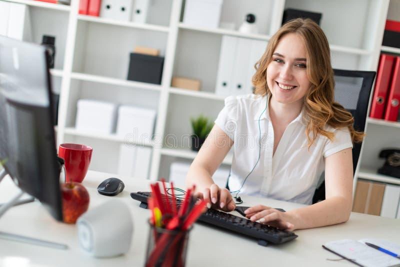 Härlig ung flicka som i regeringsställning arbetar med datoren Flickan har en skalm och en telefon framme av henne fotografering för bildbyråer