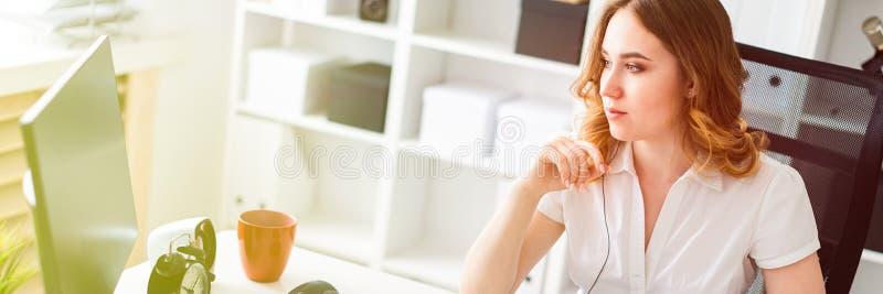 Härlig ung flicka som i regeringsställning arbetar med datoren Flickan har en skalm och en telefon framme av henne royaltyfria bilder